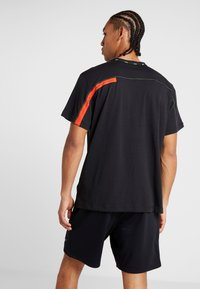 Nike Performance - DRY - T-shirts med print - black/habanero red - 2