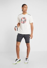Nike Performance - WILD RUN - Camiseta estampada - pale ivory - 1