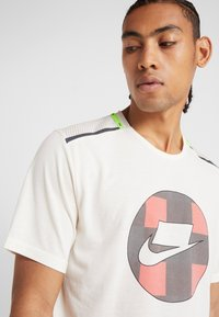 Nike Performance - WILD RUN - Camiseta estampada - pale ivory - 3