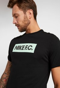Nike Performance - DRY TEE SEASONAL BLOCK - T-shirt med print - black/vapor green - 5