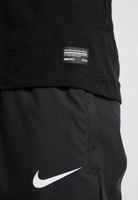 Nike Performance - DRY TEE SEASONAL BLOCK - T-shirt med print - black/vapor green - 3
