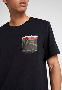 Nike Performance - TEE DNA POCKET - Camiseta estampada - black - 5