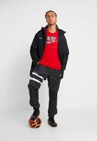 Nike Performance - DRY TEE GROUND  - Print T-shirt - sport red - 1