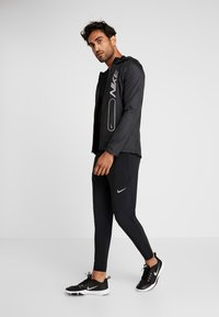Nike Performance - BRTHE RISE - Print T-shirt - black/reflective - 1