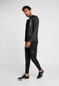 Nike Performance - BRTHE RISE - Camiseta estampada - black/reflective - 1