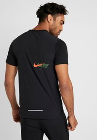Nike Performance - BRTHE RISE - Print T-shirt - black/reflective