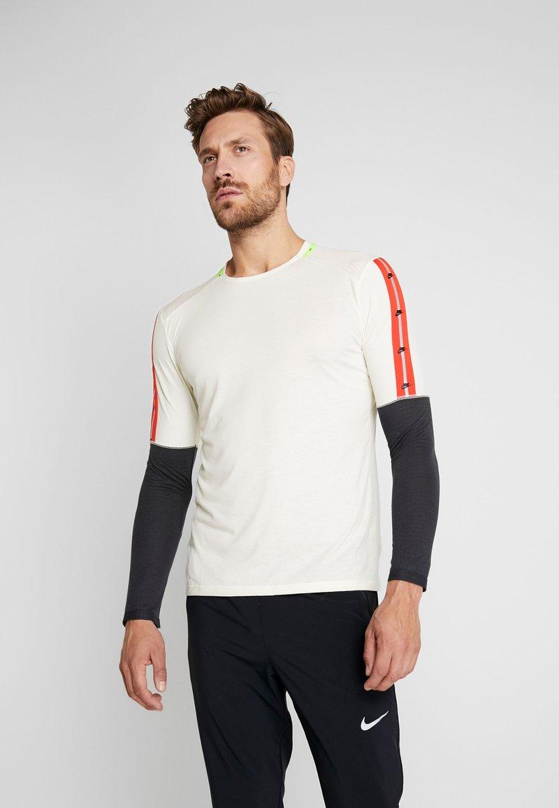 Nike Performance - WILD RUN - Funkční triko - pale ivory/off noir/black