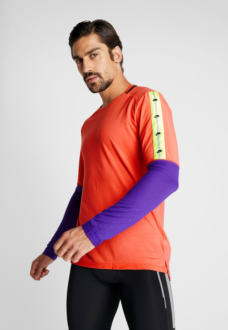 Nike Performance - WILD RUN - Camiseta de deporte - ember glow/court purple/black