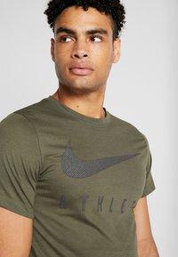 Nike Performance - DRY TEE - T-shirt med print - cargo khaki - 4