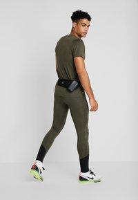 Nike Performance - DRY TEE - T-shirt med print - cargo khaki - 1
