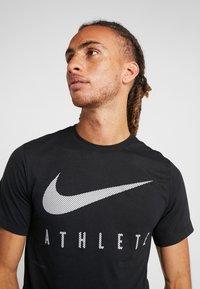 Nike Performance - DRY TEE - T-shirt med print - black - 4