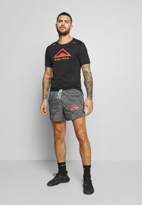 Nike Performance - RISE TRAIL - Camiseta estampada - black/laser crimson - 1