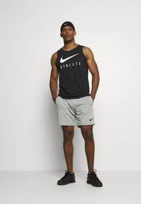 Nike Performance - TANK ATHLETE - Sports shirt - black/white - 1