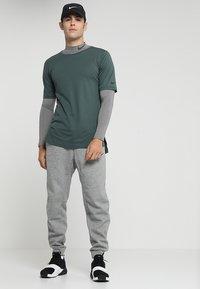 Nike Performance - PANT TAPER - Verryttelyhousut - dark grey heather/black - 1