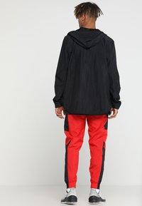 Nike Performance - RETRO PANT  - Tracksuit bottoms - university red/black - 2