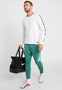 Nike Performance - FC PANT - Teplákové kalhoty - bicoastal/white - 1