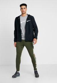Nike Performance - CAMO - Tracksuit bottoms - cargo khaki/black - 1