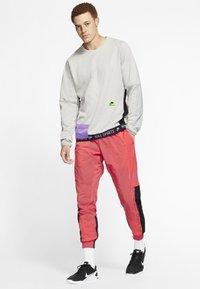 Nike Performance - FLEX PANT - Pantalon de survêtement - orange - 1