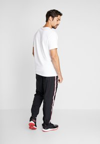 Nike Performance - THROWBACK PANT  - Tracksuit bottoms - black/white - 2