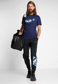 Nike Performance - THERMA PANT TAPER - Pantalones deportivos - black/white - 1