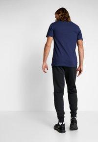 Nike Performance - THERMA PANT TAPER - Pantalones deportivos - black/white - 2