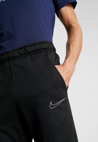 Nike Performance - THERMA PANT TAPER - Pantalones deportivos - black/white - 3