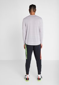 Nike Performance - WILD RUN PANT - Träningsbyxor - black/electric green/habanero red - 2