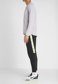 Nike Performance - WILD RUN PANT - Träningsbyxor - black/electric green/habanero red - 3