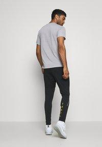 Nike Performance - PANT TRAIL - Verryttelyhousut - black/laser crimson - 2