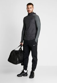 Nike Performance - UTILITY THRMA NVTY - Camiseta de deporte - dark smoke grey/black - 1