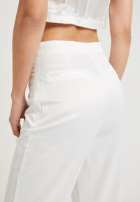 NA-KD - SHINY FLARE SUIT PANTS - Trousers - white - 4