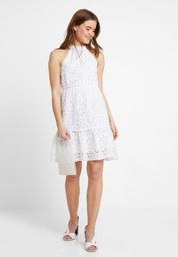 NA-KD - GRADUATION DROP HIGH NECK ANGLAISE DRESS - Denní šaty - white - 1