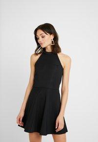 NA-KD - PAMELA REIF X  NA-KD HALTER NECK SKATER DRESS - Jersey dress - black - 0