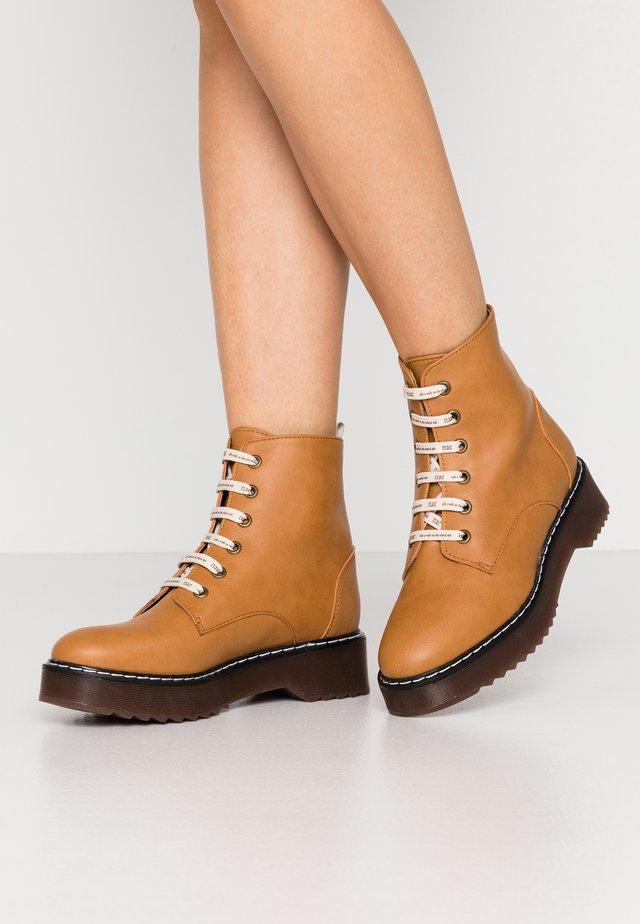 TRINA - Kotníkové boty na platformě - camel