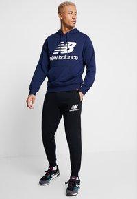 New Balance - ESSENTIALS STACKED LOGO - Pantalon de survêtement - black - 1