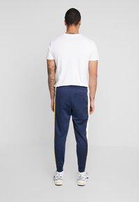 New Balance - NB ATHLETICS TRACK PANT - Spodnie treningowe - natindgo - 2