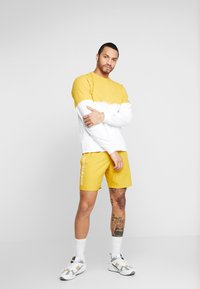 New Balance - NB ATHLETICS WIND SHORT - Shorts - varsgold - 1