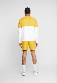 New Balance - NB ATHLETICS WIND SHORT - Shorts - varsgold - 2