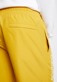 New Balance - NB ATHLETICS WIND SHORT - Shorts - varsgold - 6