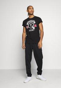 New Era - NFL GRAPHIC HELMET TEE OAKLAND RAIDERS - Club wear - black - 1