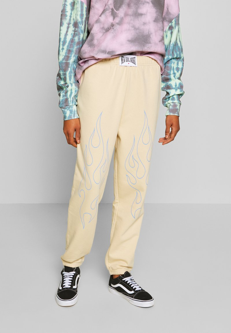NEW girl ORDER - OUTLINE FLAME JOGGERS - Tracksuit bottoms - beige