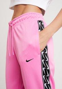 Nike Sportswear - JOGGER LOGO TAPE - Tracksuit bottoms - china rose/black - 6