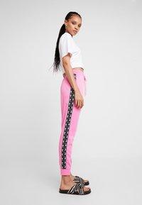 Nike Sportswear - JOGGER LOGO TAPE - Tracksuit bottoms - china rose/black - 4
