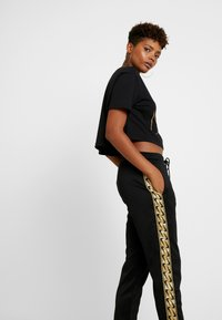 Nike Sportswear - JOGGER LOGO TAPE - Tracksuit bottoms - black/gold - 4