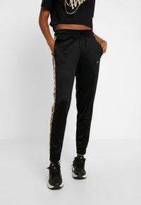 Nike Sportswear - JOGGER LOGO TAPE - Tracksuit bottoms - black/gold - 0