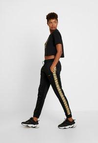 Nike Sportswear - JOGGER LOGO TAPE - Tracksuit bottoms - black/gold - 2