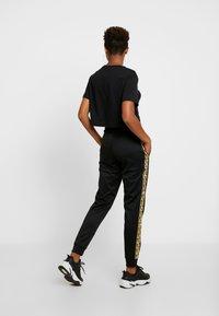 Nike Sportswear - JOGGER LOGO TAPE - Tracksuit bottoms - black/gold - 3