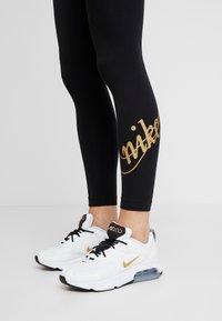 Nike Sportswear - GLITTER - Leggings - black/gold - 3