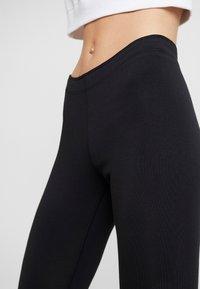 Nike Sportswear - GLITTER - Leggings - black/gold - 5