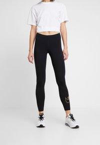 Nike Sportswear - GLITTER - Leggings - black/gold - 0